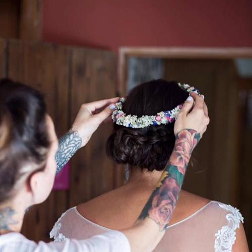 Final touches adding the flower crown to this beautiful boho bridal hair